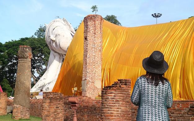 アントン県のワットクンインタプラムン寺院でタイ最大の涅槃仏像を見上げる女性訪問者