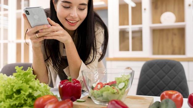 Женский видеоблогер дома фотографирует со смартфоном