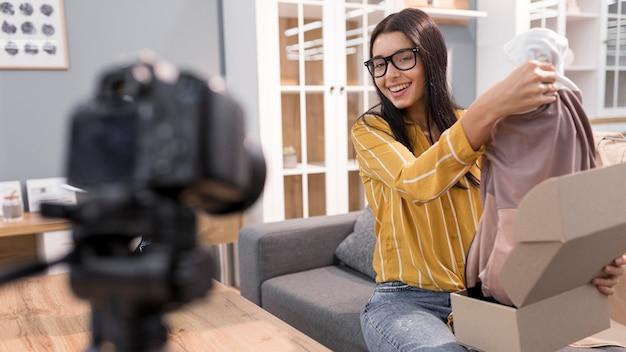Женский видеоблогер дома распаковывает одежду с камерой