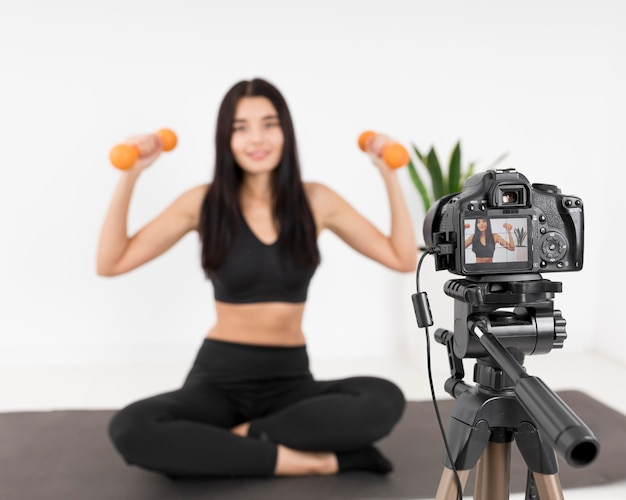 Женский видеоблогер дома с камерой, тренирующейся с весами