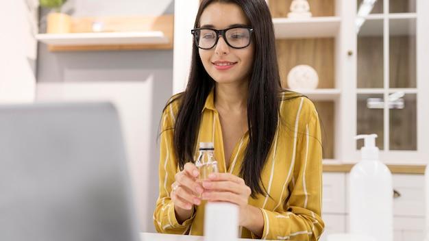 Женский видеоблогер дома с продуктом и ноутбуком