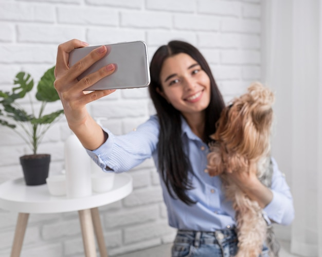 Женский видеоблогер дома со смартфоном и собакой