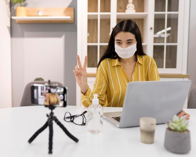Женский видеоблогер дома со смартфоном и ноутбуком