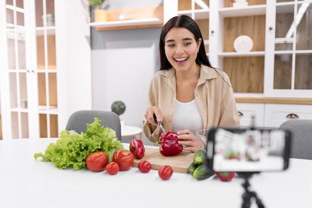 야채와 스마트 폰으로 집에서 여성 동영상 블로거