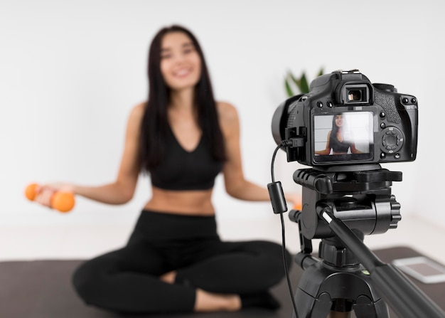 Female vlogger at home with camera exercising