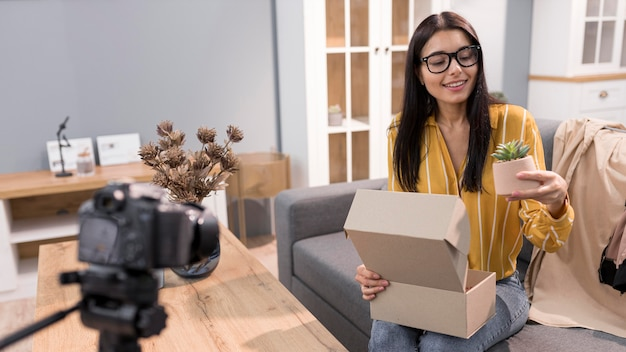 Female vlogger at home with camera unboxing plant