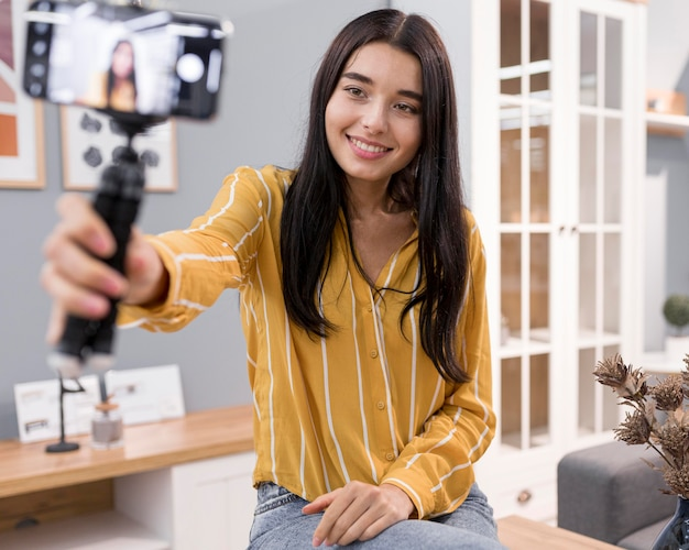 Female vlogger at home with smartphone
