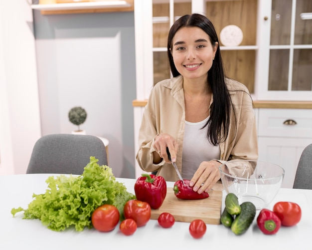 Female vlogger at home with vegetables