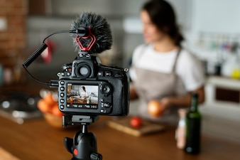 Female vlogger recording cooking related broadcast at home