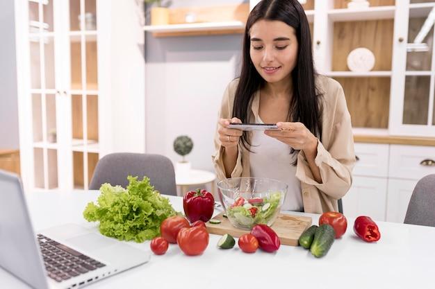 Vlogger femminile che registra video con laptop e smartphone