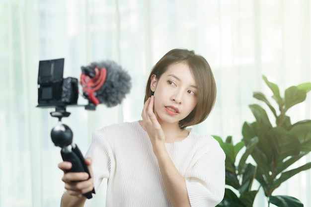 Female vlogger recording with a camera at home