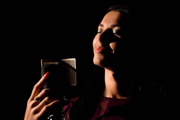 Female vocal artist singing in a recording studio.