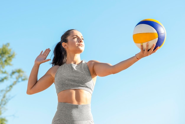 Female volleyball player serving ball in the beginning of game
