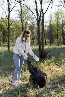 女性ボランティアが公園のプラスチックのゴミを掃除します。ボランティアは世界をきれいにします