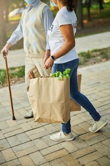 야채와 과일 한 봉지를 배달하는 여성 자원 봉사자