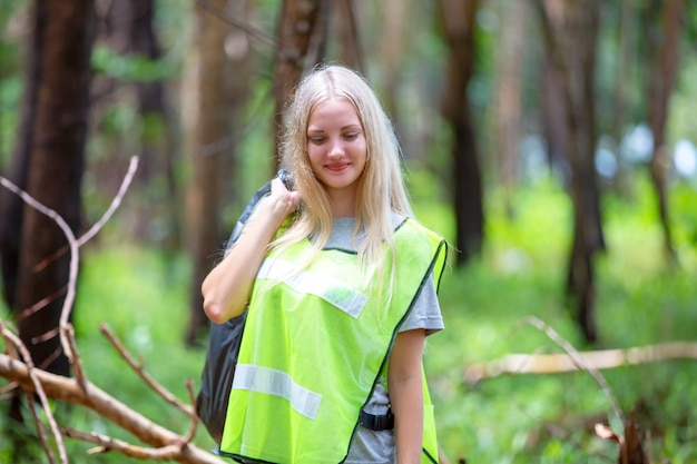 Женщина-волонтер держит пластиковый мешок для мусора, собирает мусор и кладет его в черный мешок для мусора.