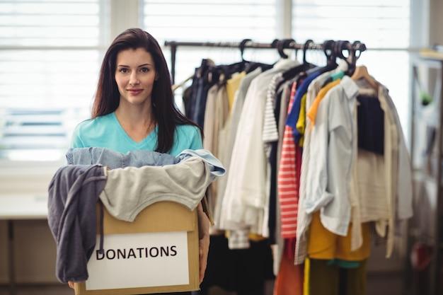 Женский добровольца держа одежду в ящик для пожертвований