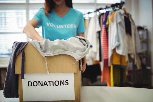 기부금 상자에 여성 자원 봉사 지주 옷