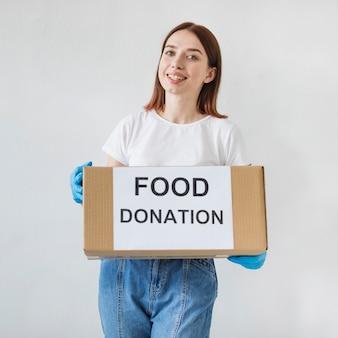 募金箱を保持している女性ボランティア