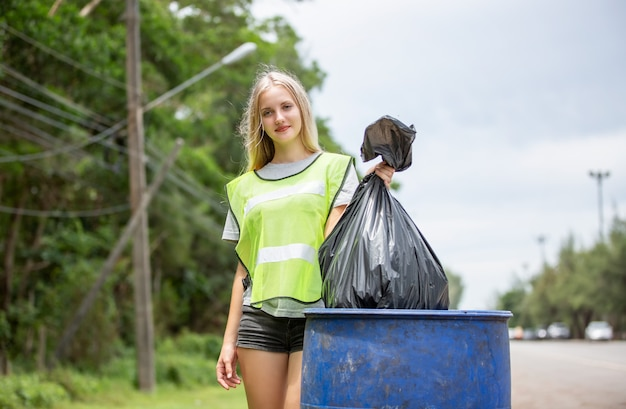 Female volunteer holding a plastic waste bag, picking up the garbage and putting it in a black garbage bag.