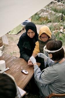 여성 자원 봉사자 또는 의사가 어린 소녀에게 예방 접종을