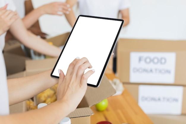 Женщина-волонтер с помощью планшета готовит коробки с едой