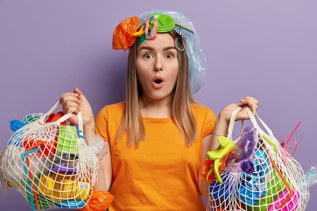 驚愕の表情をした女性ボランティア、ゴミ拾い、ネットバッグ2個、オレンジ色のtシャツを着て、領土全体を掃除したなんて信じられない、紫色の壁に立ち、ゴミをリサイクル
