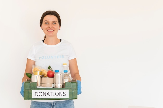 Female volunteer with gloves handling box of food donations