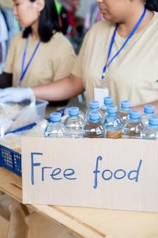 물과 함께 무료 음식과 플라스틱 병을 기부하는 여성 자원 봉사자