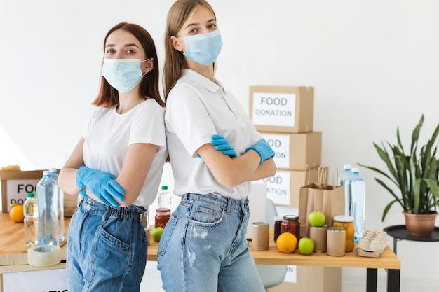 Женщины-добровольцы позируют в медицинских масках и перчатках