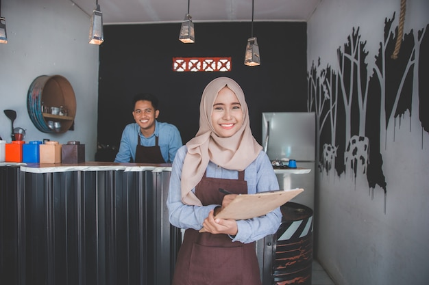 Female waiter in apron writing order