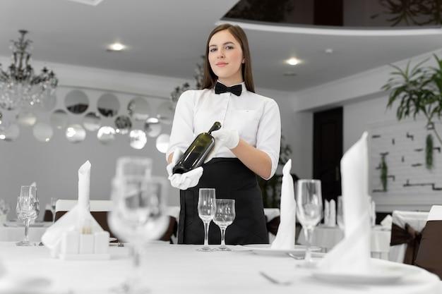 Женский официант держит бутылку вина в ресторане.