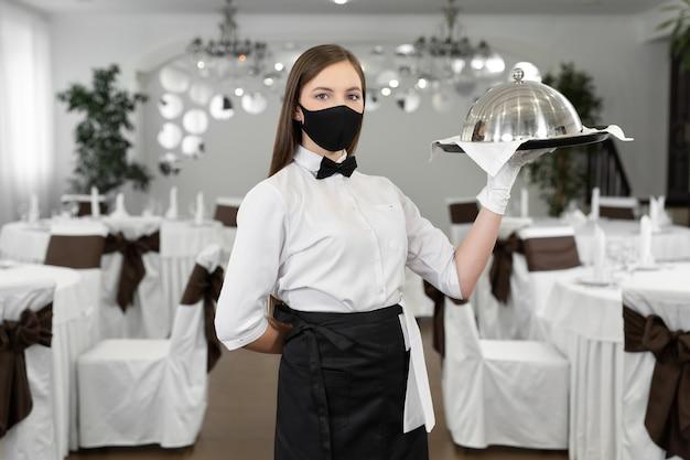 保護用医療マスクを着用した女性ウェイターは、ホットディッシュの入った閉じたトレイを持っています。