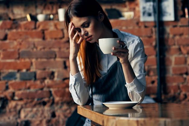 Официант женского пола в фартуке заказ обслуживания чашки кофе