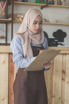 Женский официант в порядке написания фартук