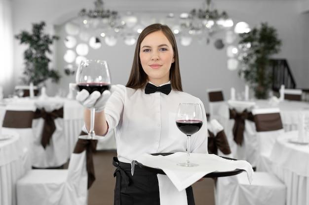 Официантка в белых перчатках держит бокал и бутылку красного вина.