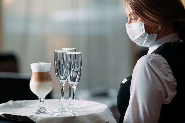 Официантка европейской внешности в медицинской маске подает кофе латте.