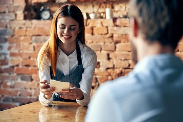 커피 한 잔을 들고 있는 여성 웨이터가 고객에게 서비스를 제공합니다.