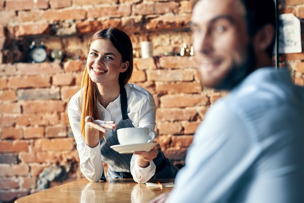 顧客カフェを提供するコーヒーのカップを持つ女性ウェイター