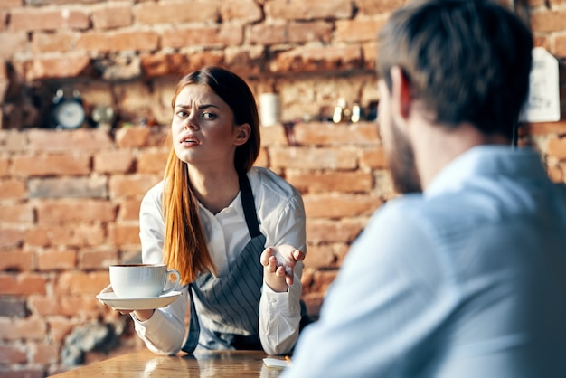 Female waiter with a cup of coffee serving customer cafe