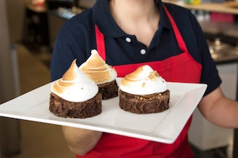 Female waitress holding chocolate cake with whipped cream in tray