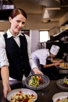Female waitress holding plates with food in kitchen