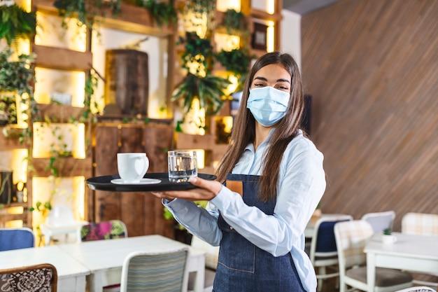 의료 보호 마스크의 여성 웨이트리스는 새로운 정상 개념을 나타내는 레스토랑 durin 코로나 바이러스 전염병에서 커피를 제공합니다.