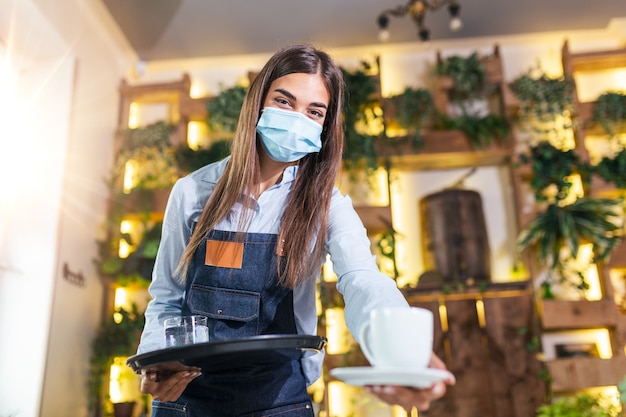 Female waitress in a medical protective mask serves the coffee in restaurant durin coronavirus pandemic representing new normal concept