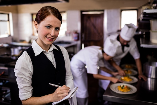 Female waitress noting an order on notepad in kitchen