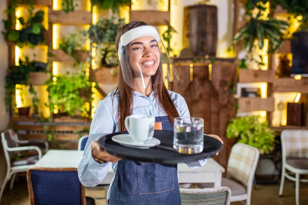 Female waitress wearing face shield, visor serves the coffee in restaurant during coronavirus pandemic . holding tray with cup of coffee, working in cafeteria and serves the table