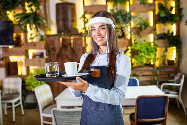 Female waitress wearing face shield, visor serves the coffee in restaurant during coronavirus pandemic representing new normal concept