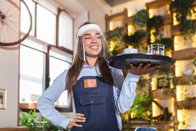 얼굴 방패를 착용 한 여성 웨이트리스, 바이저는 새로운 정상 개념을 나타내는 코로나 바이러스 전염병 동안 레스토랑에서 커피를 제공합니다.
