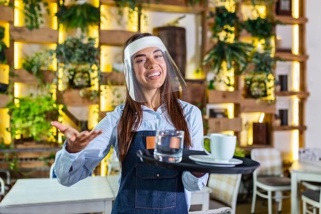 Female waitress wearing face shield