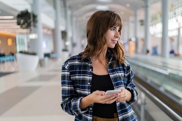 Donna che cammina attraverso l'aeroporto utilizzando il suo dispositivo smartphone.